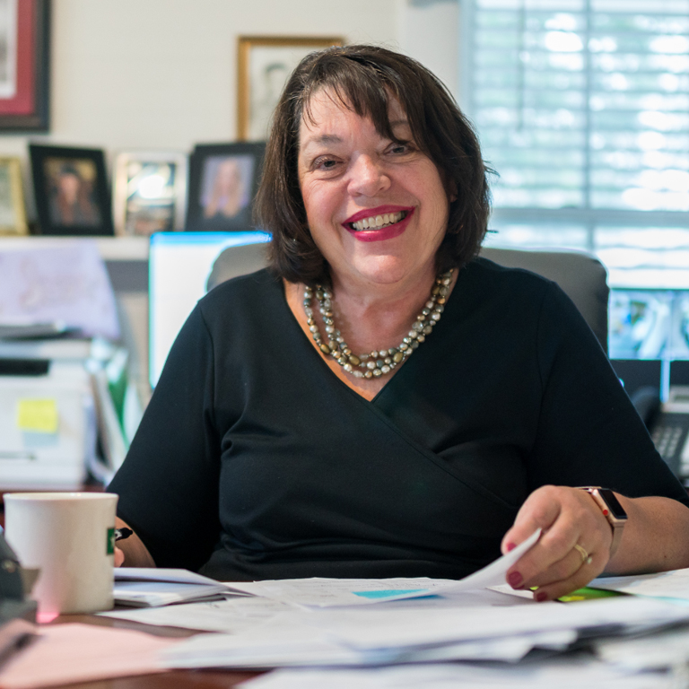 Judy Crowley, director of Family Services of Coffee County, smiles from behind her desk while reviewing papers