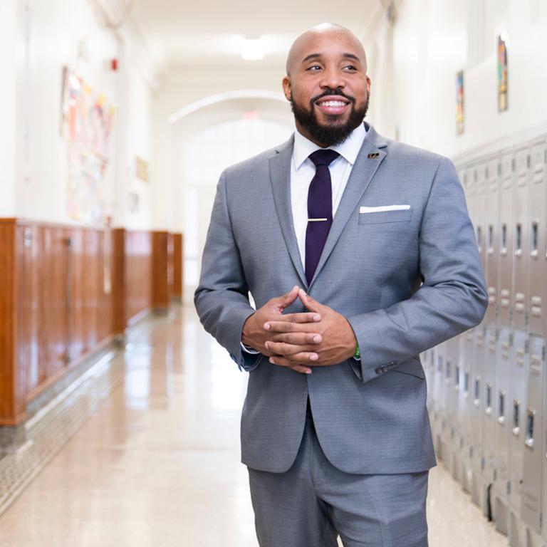 James Thompson, president of 100 Black Men of America's Washington, D.C., chapter, poses in a school hallway between lockers