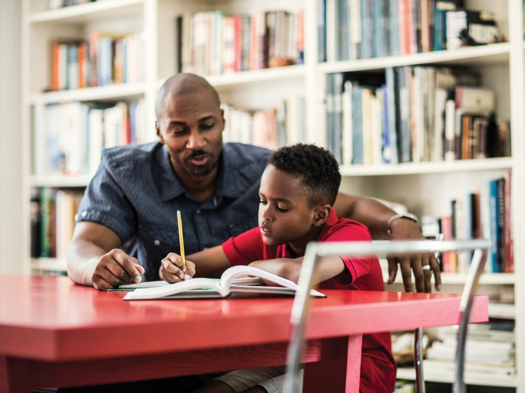 African American man sitting at a table helping a young boy with schoolwork