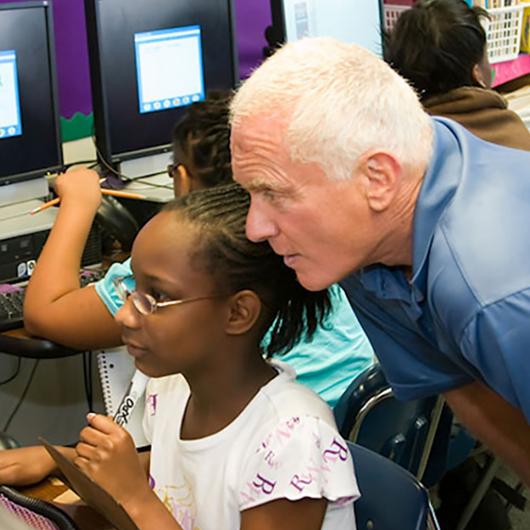 Harris Rosen of Rosen Hotels & Resorts helps a student at a computer