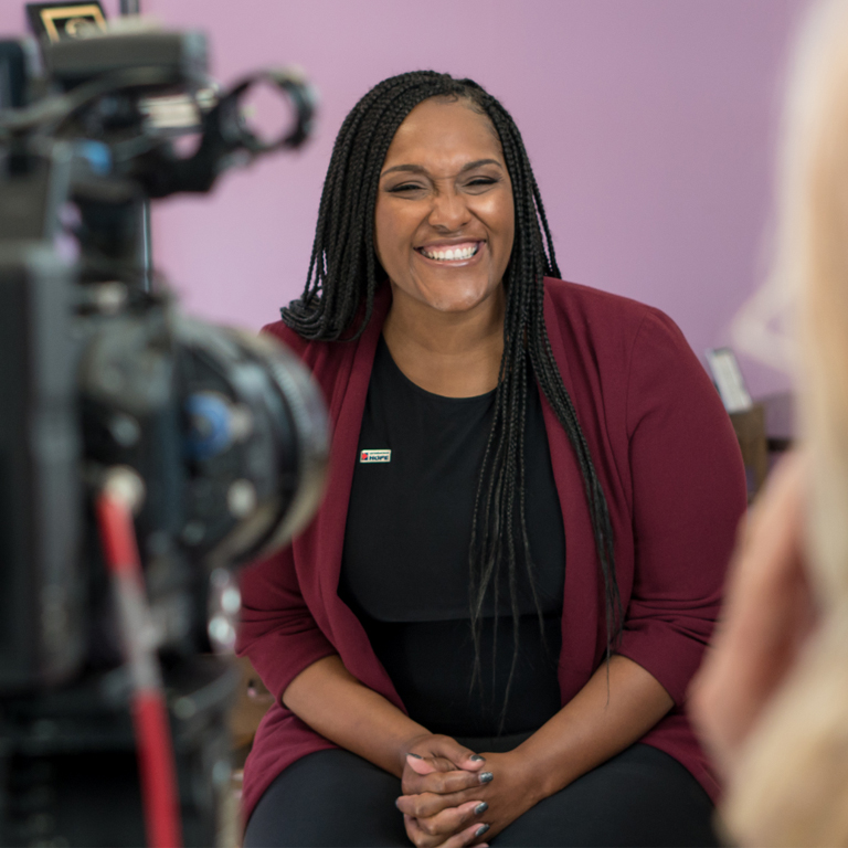 LaWanna Ross, financial wellness coach with Operation HOPE, smiles on the set of a video shoot