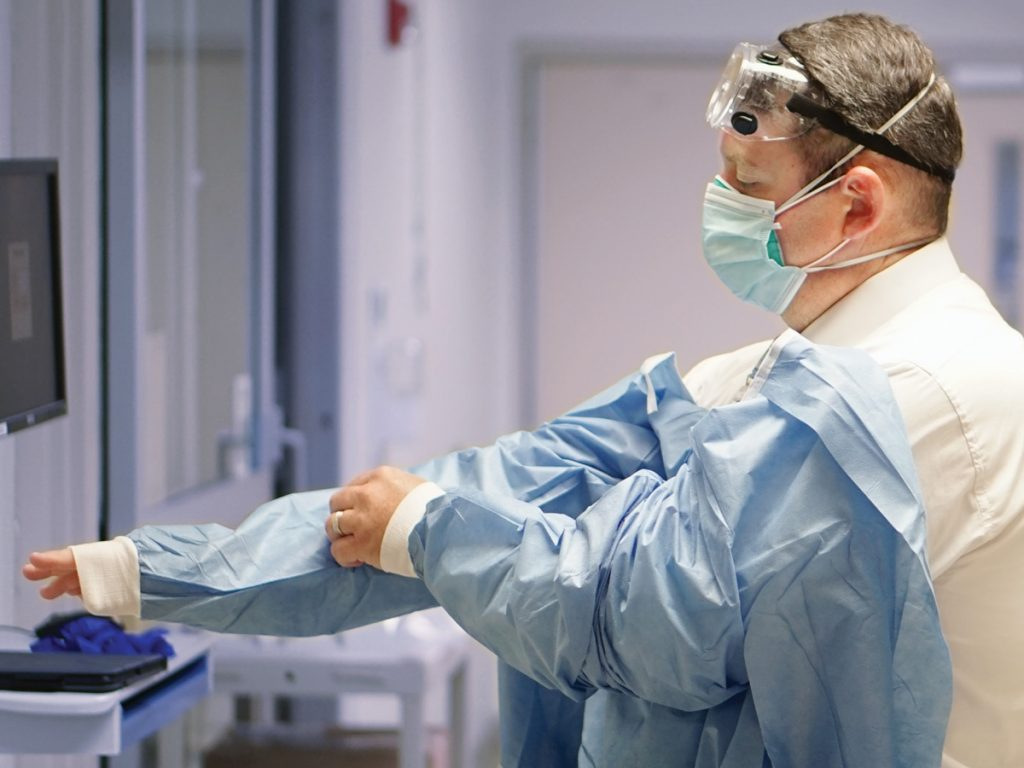 Worker at Phoebe Health putting on scrubs